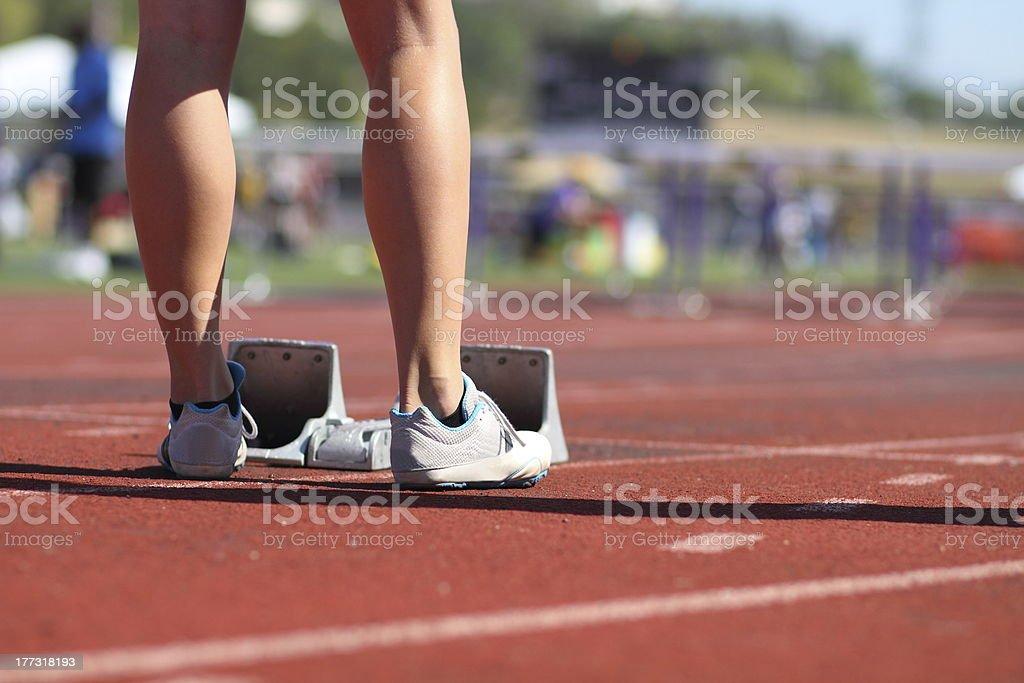 Female athlete sprinter behind starting block stock photo