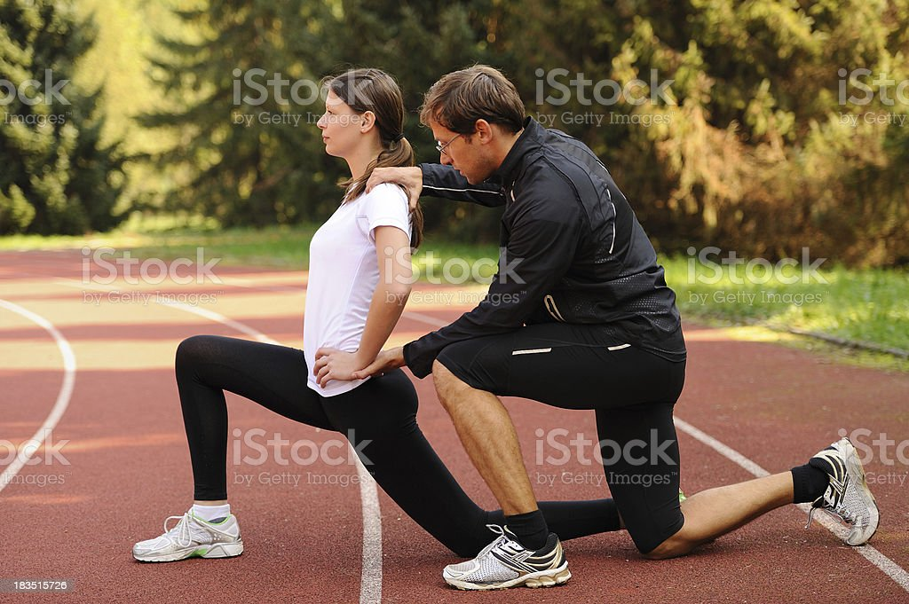 Female athlete stretching assisted by her trainer royalty-free stock photo
