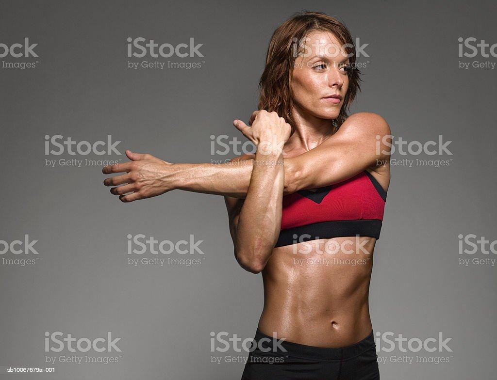 Female athlete stretching, studio shot stock photo