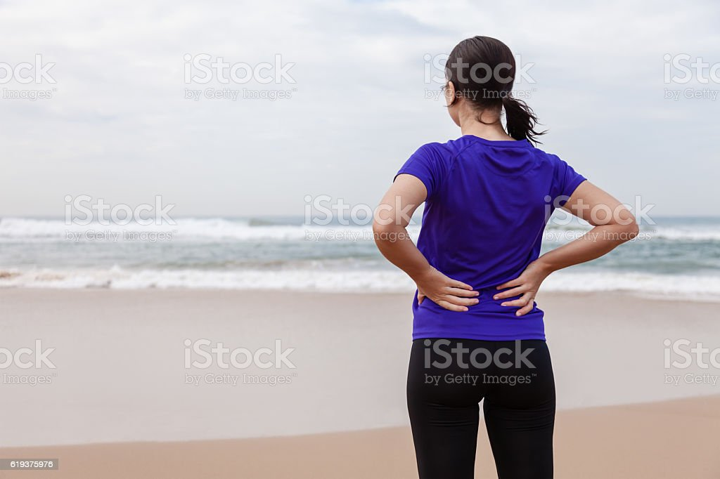 Female athlete suffering from a back injury at the beach stock photo