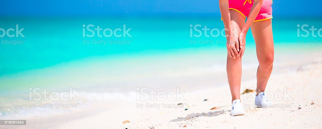 Female Athlete Suffering From Pain In Leg While Exercising stock photo