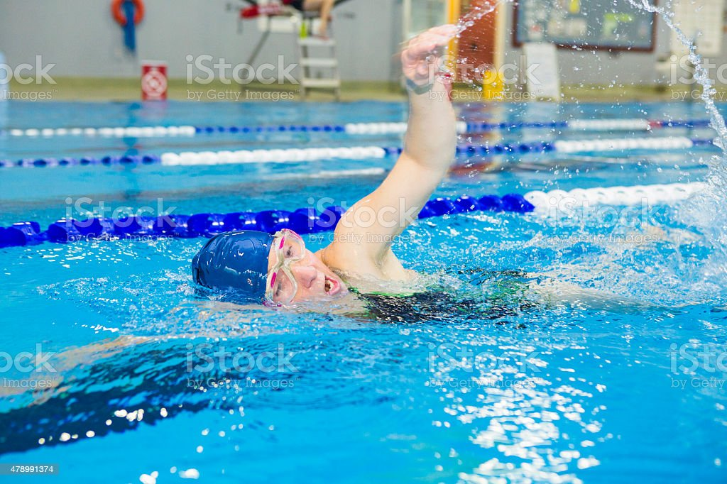Female athlete swimming in indoor pool stock photo