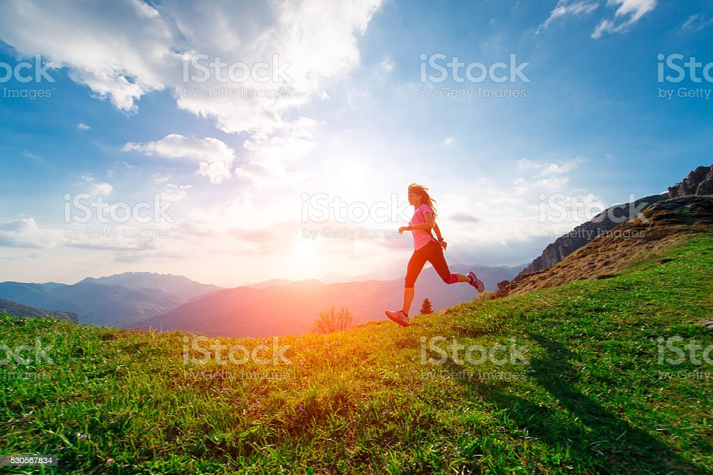 Female athlete trains running in the hillside meadows at sunset stock photo