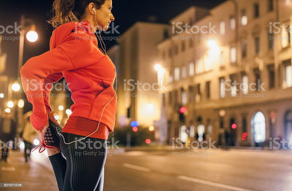Female Athlete Warming up for a Late Night Jogging stock photo