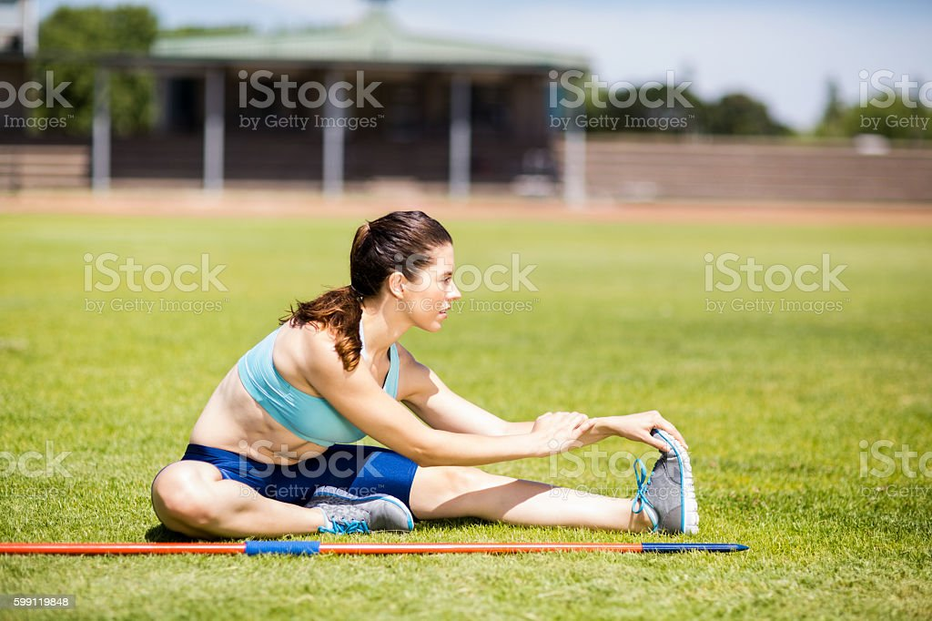 Female athlete warming up in stadium stock photo