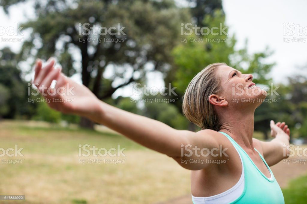 Female athlete with arms outstretched in park royalty-free stock photo