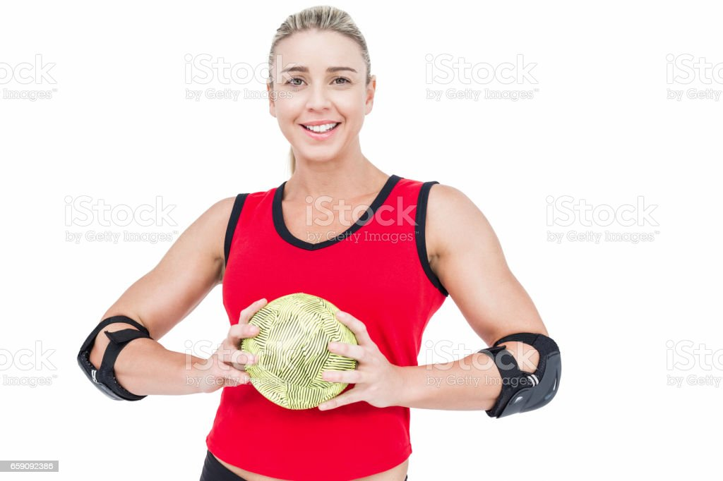 Female athlete with elbow pad holding handball stock photo