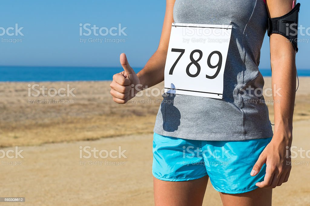 Female athlete with race start number doing thumbs up. photo libre de droits