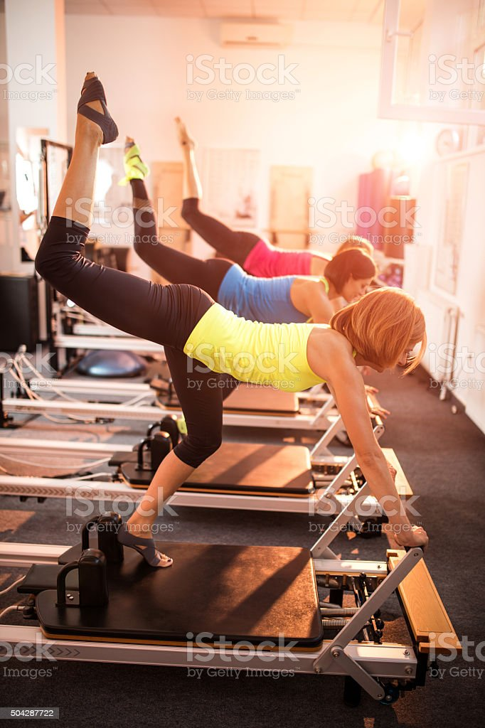 Female athletes exercising with their legs up on Pilates machine stock photo