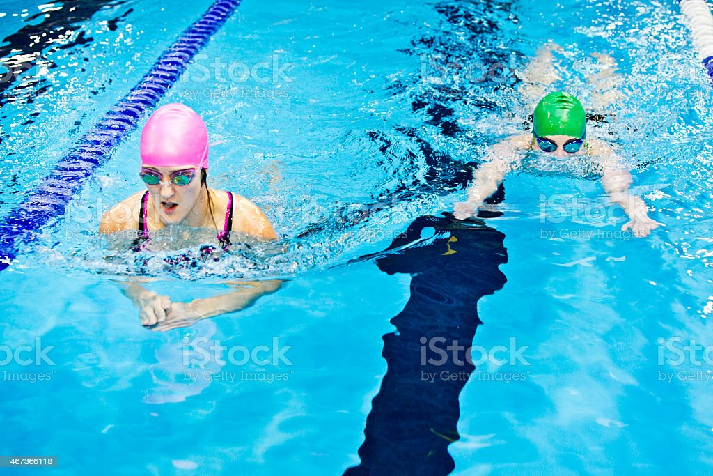 Female athletes swimming in indoor pool stock photo