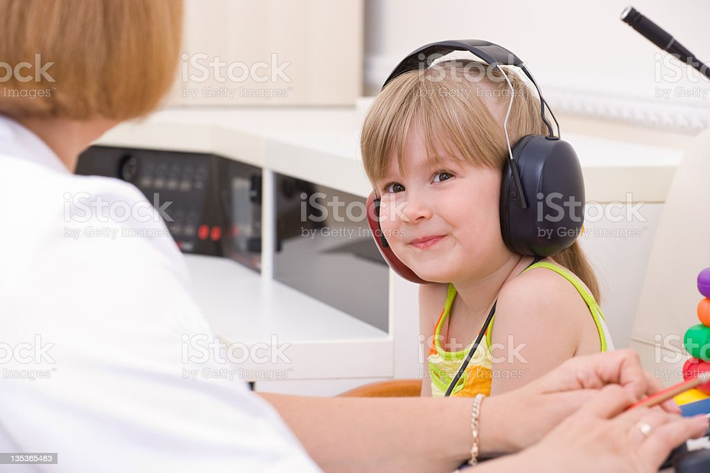 Female audiologist testing a young girls hearing stock photo