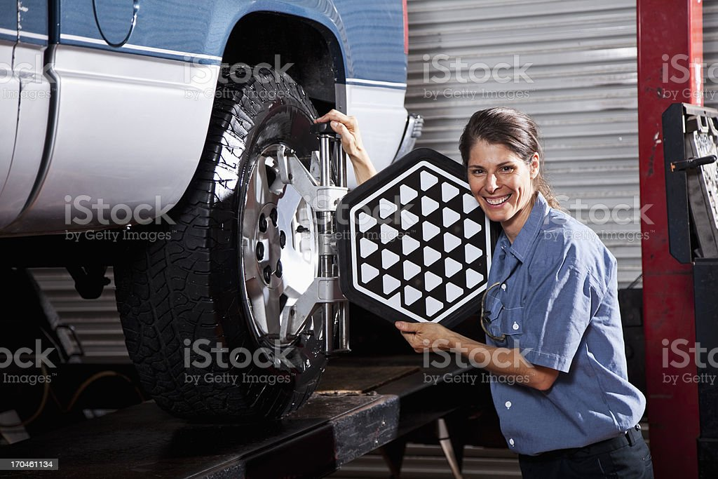 Female auto mechanic doing wheel alignment royalty-free stock photo
