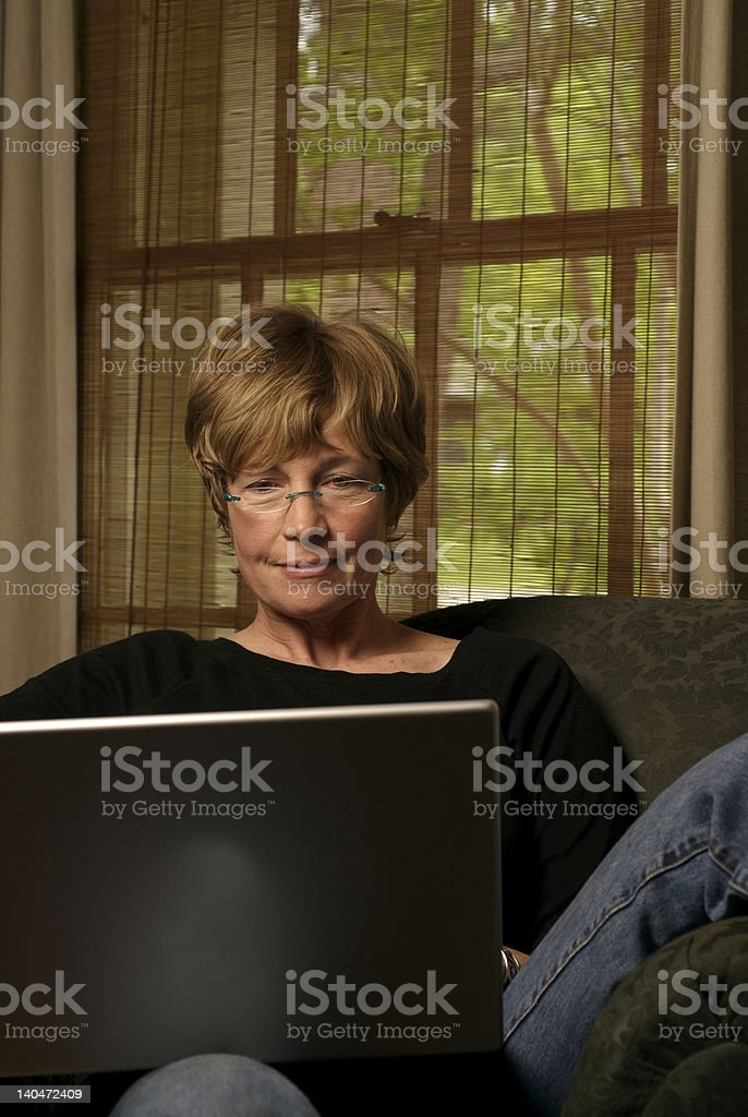 Female Baby Boomer Enjoys Wireless Laptop Internet Access royalty-free stock photo