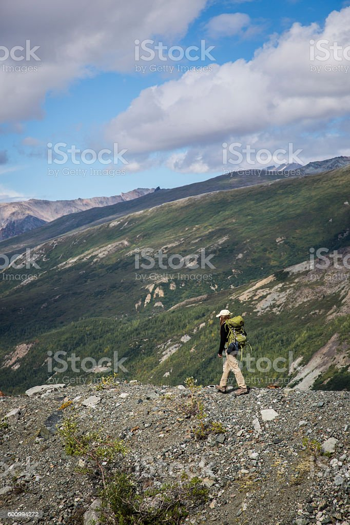 Female Backpacker hiking on Mountain Ridge in remote wilderness stock photo