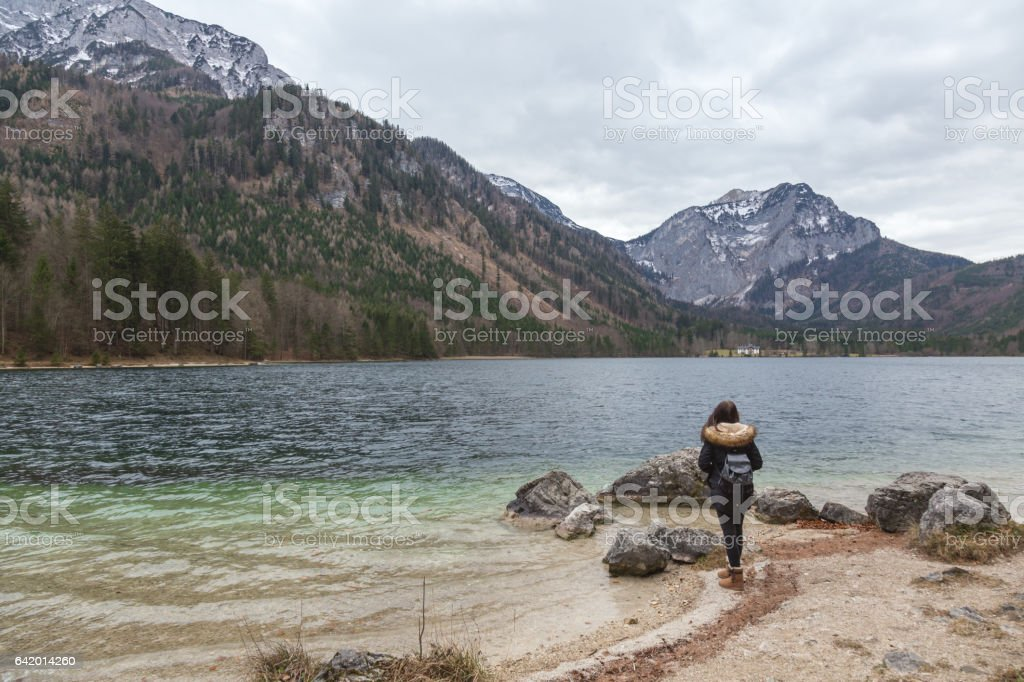 Female backpacker standing on a Langbathsee lake shore stock photo