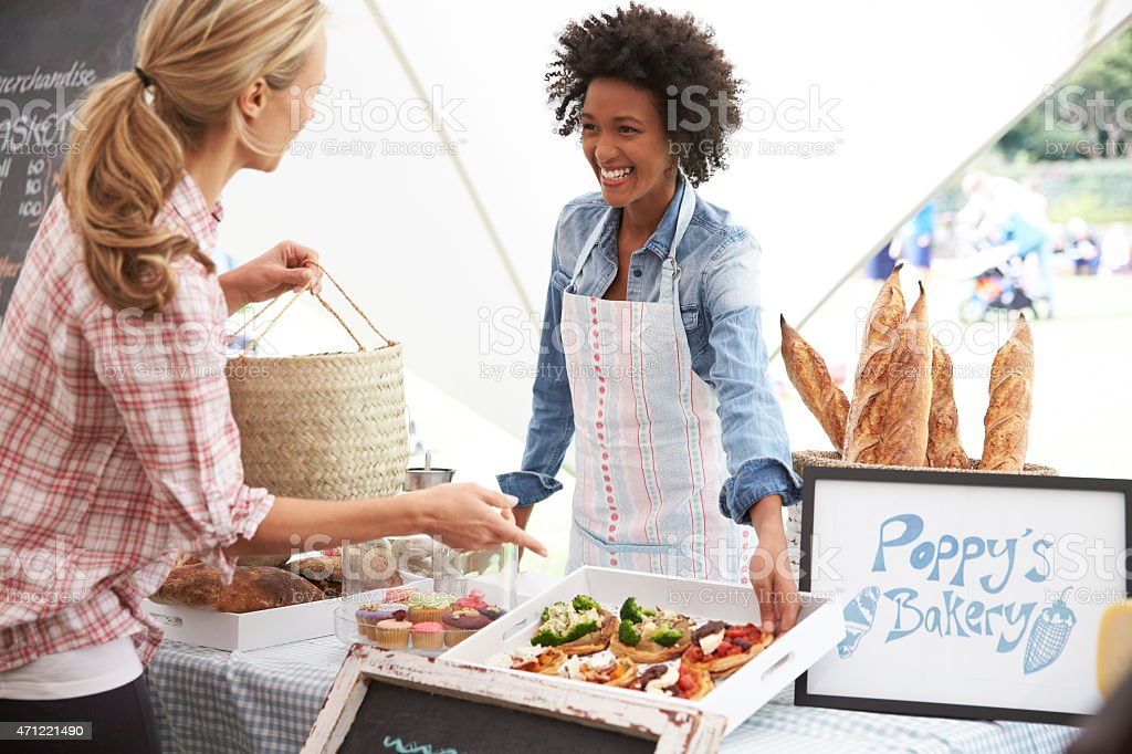 A female bakery stall holder serving customers at the market stock photo