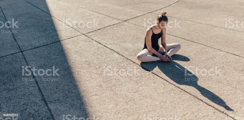 Female ballet dancer warming up before the practice stock photo