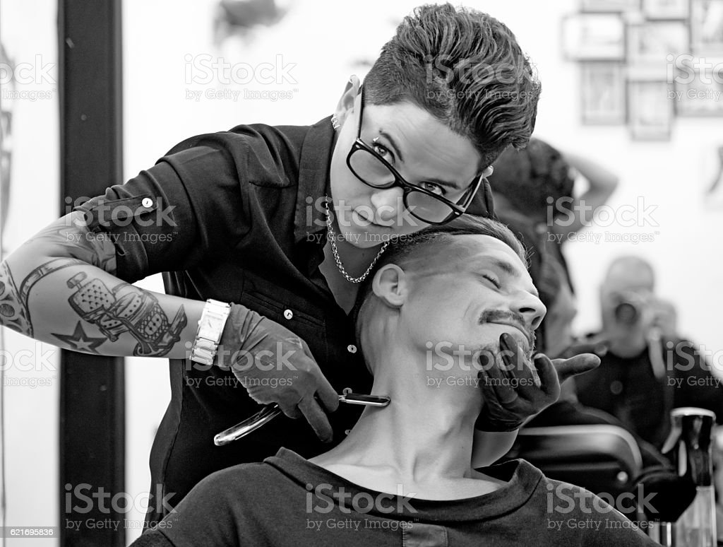 Female barber tattooed woman styling attractive threatening moustachioed male victim stock photo