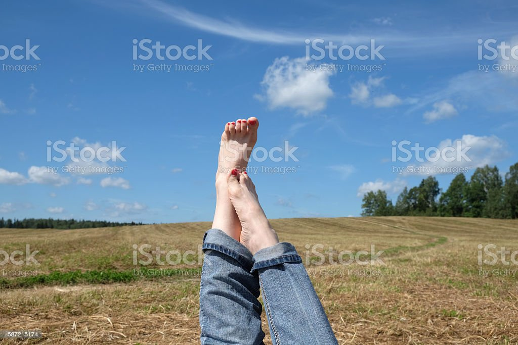 Female bare feet with red nails against summer landscape stock photo