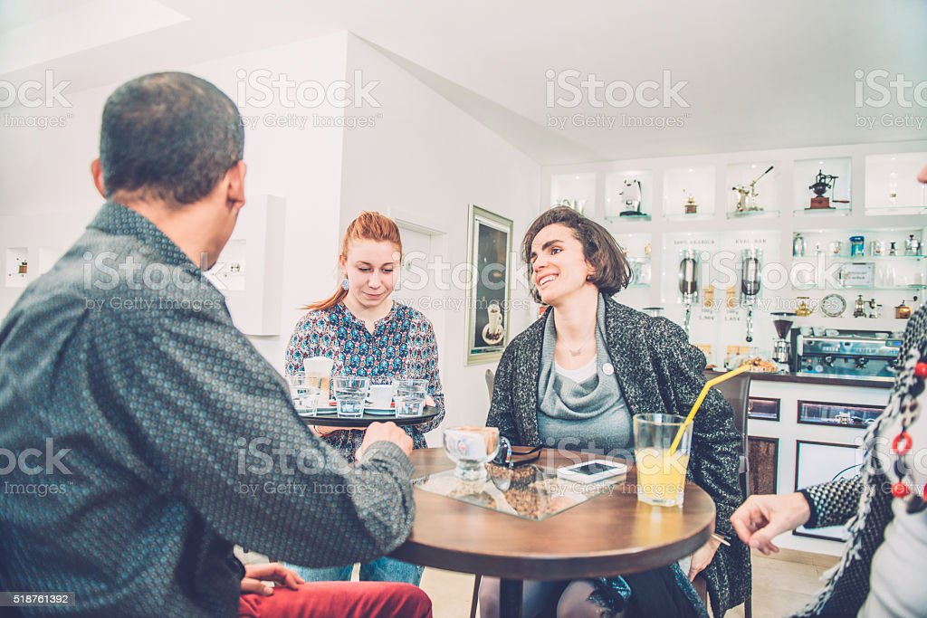 Female Barista Bringing Coffee to Three Friends, Caffe Trieste, Europe stock photo