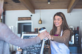 Female barista handing cup of coffee to a patron