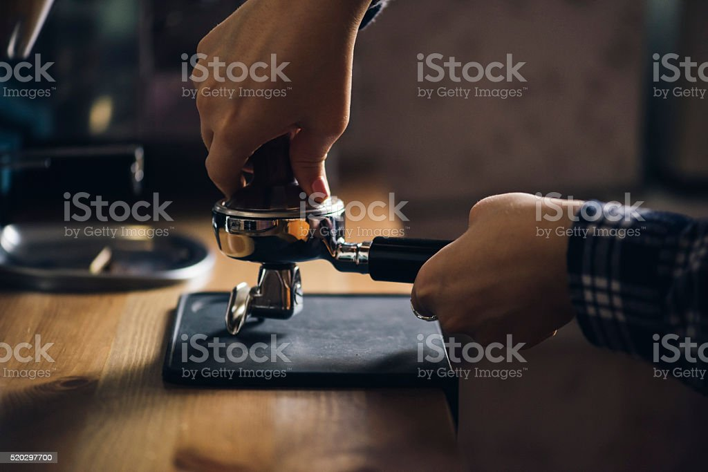 Female barista tamping coffee in a portafilter stock photo