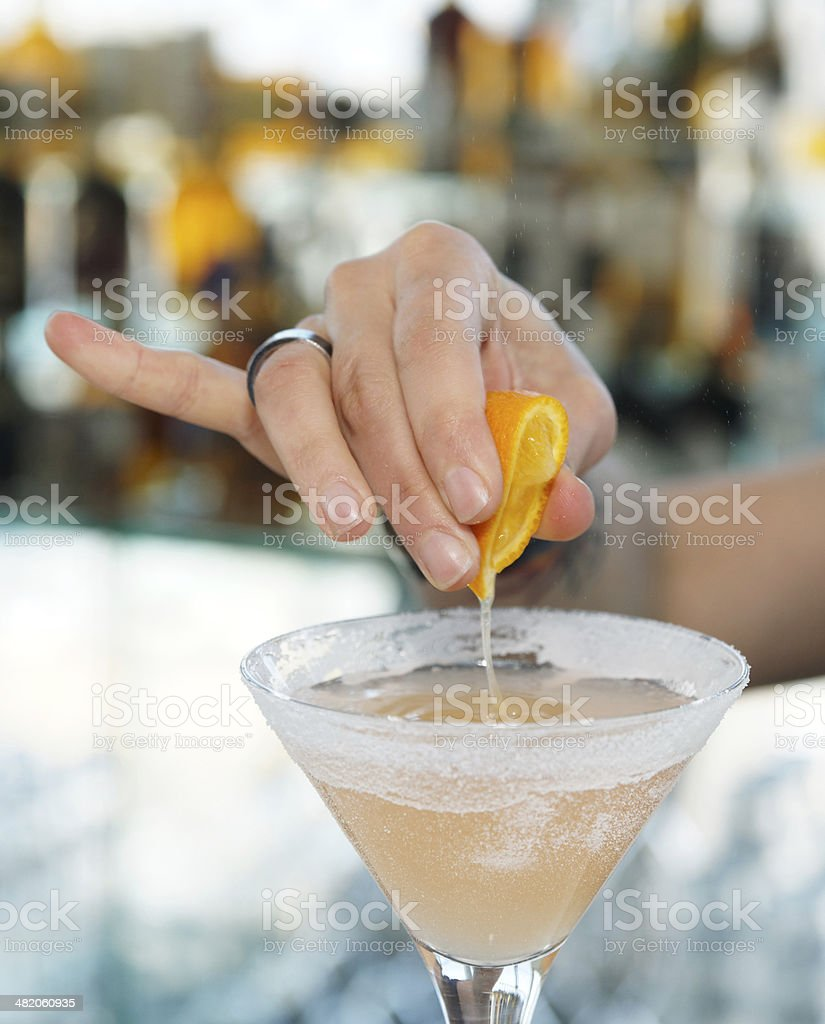 Female bartender is squeezing orange juice into glass royalty-free stock photo