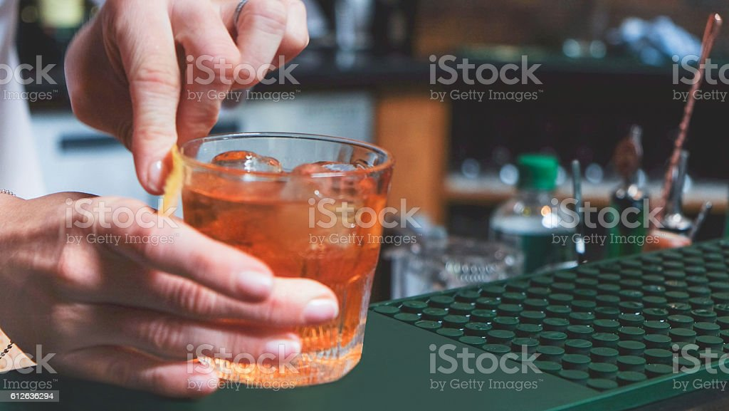 Female bartender making whiskey cocktail stock photo