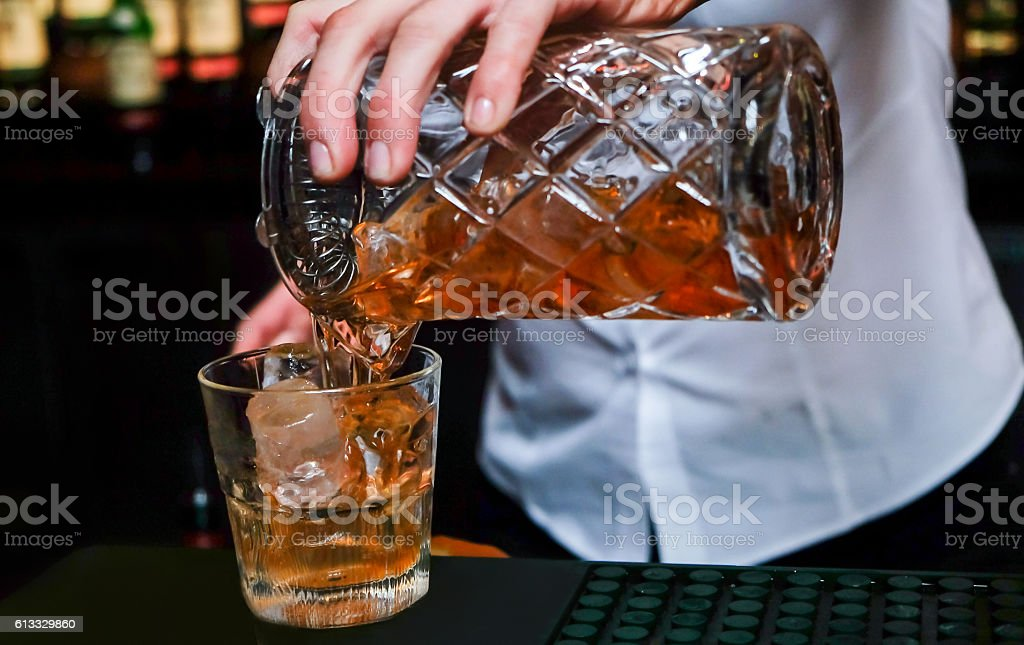 Female bartender pouring scotch Whiskey stock photo