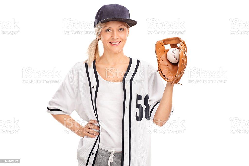 Studio shot of a female baseball player holding a ball in a baseball...