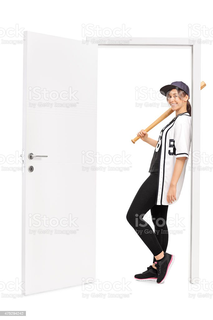 Female baseball player leaning on a door stock photo
