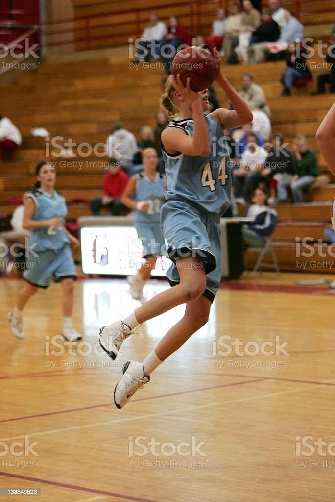 Female Basketball Player in Blue Goes Vertical in the Lane stock photo