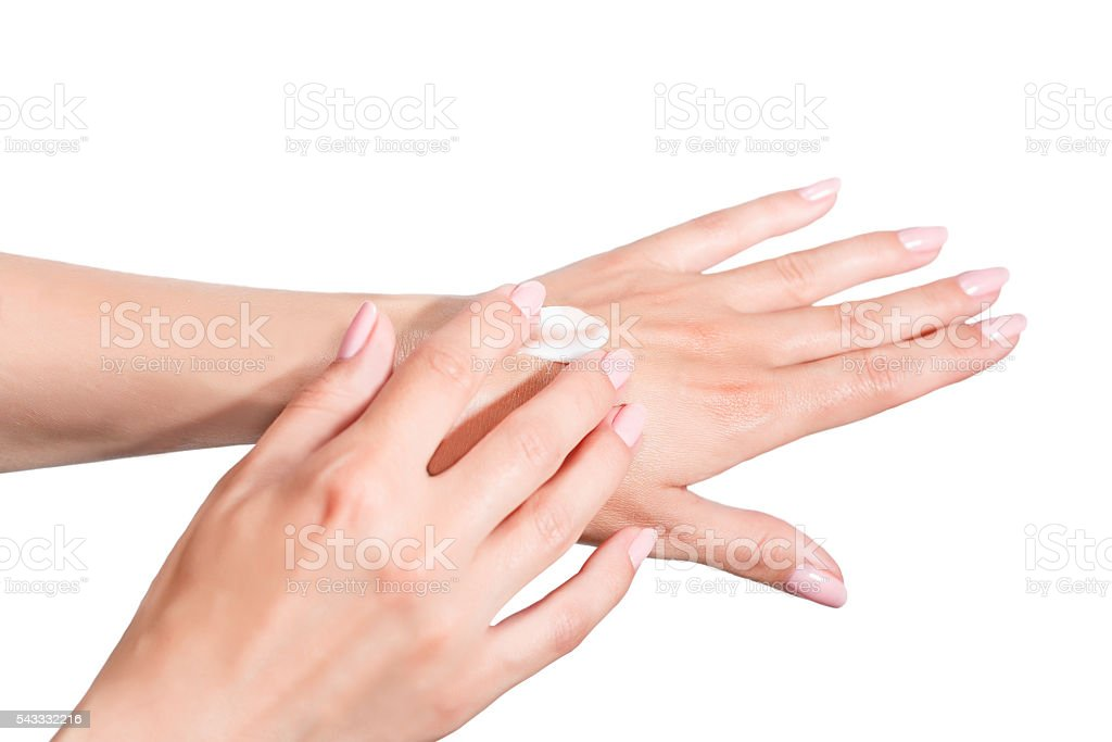 Female beautiful delicate manicured hands with moisturizing cream stock photo