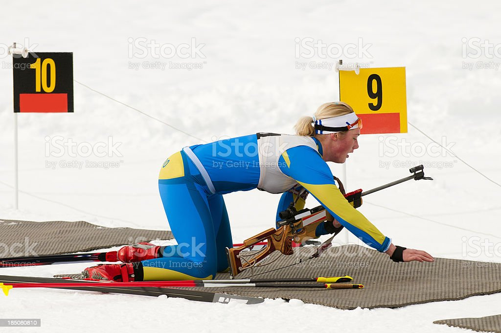 Female biathlon competitor preparing for target shooting stock photo