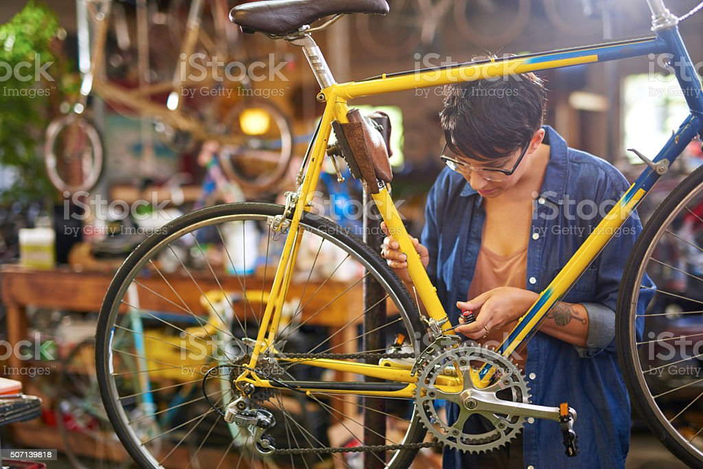 Female bicycle mechanic repairing bicycle stock photo