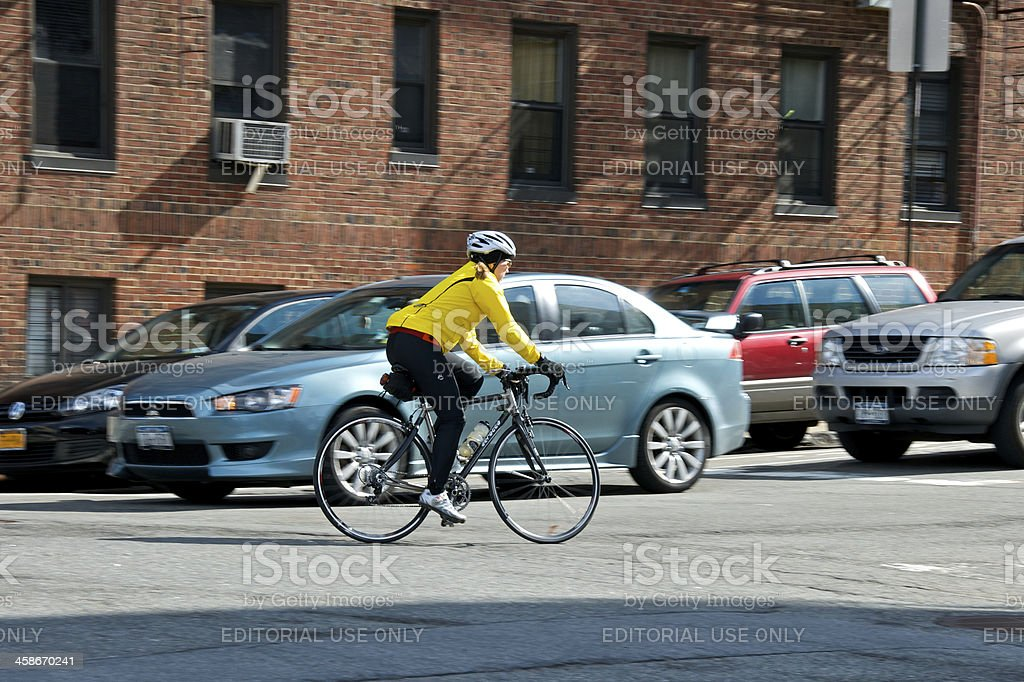 Female Bicyclist approaching bike lane, Upper Manhattan, NYC stock photo