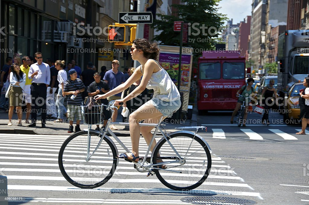 'Female Bicyclist & pedestrians at E.23rd St, Manhattan, NYC' stock photo