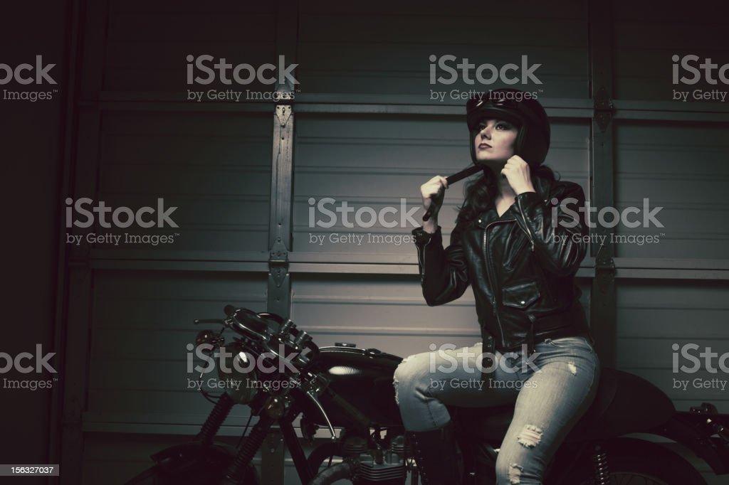 female biker fastening helmet stock photo