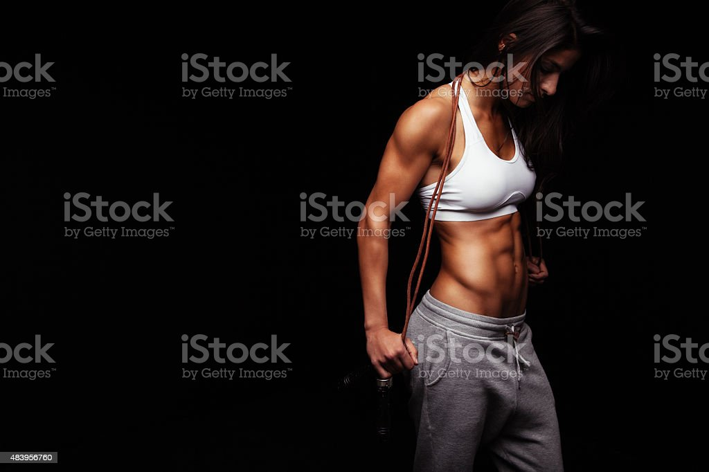 Female bodybuilder holding skipping rope stock photo