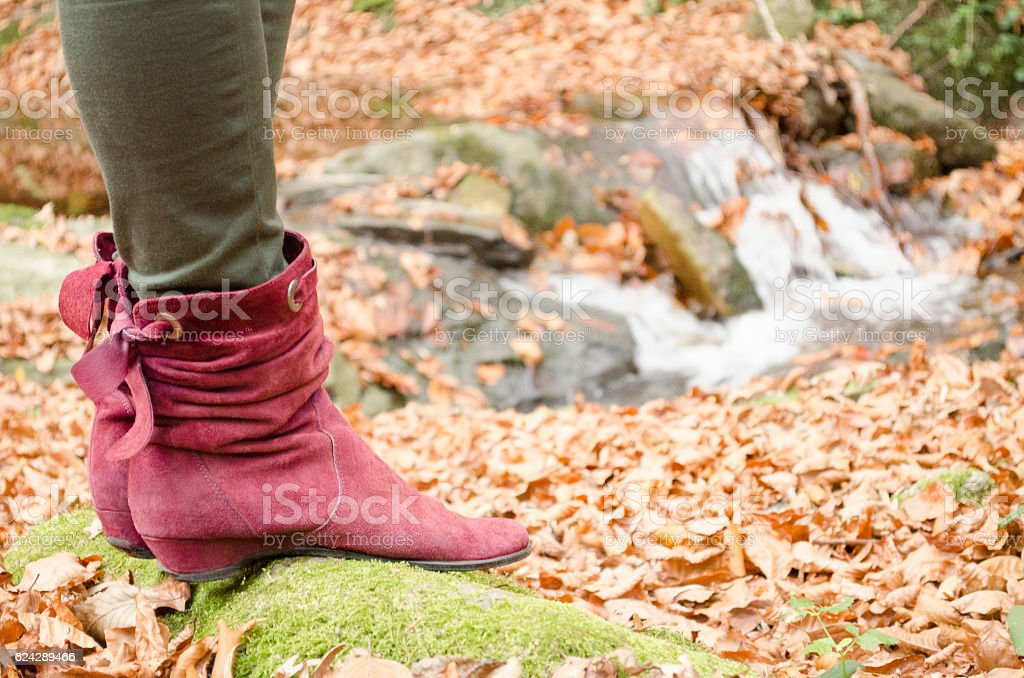 Female boots through a stream in the autumn royalty-free stock photo