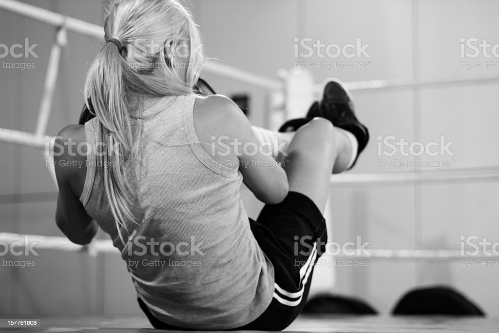 Female boxer doing sit-ups in the ring royalty-free stock photo
