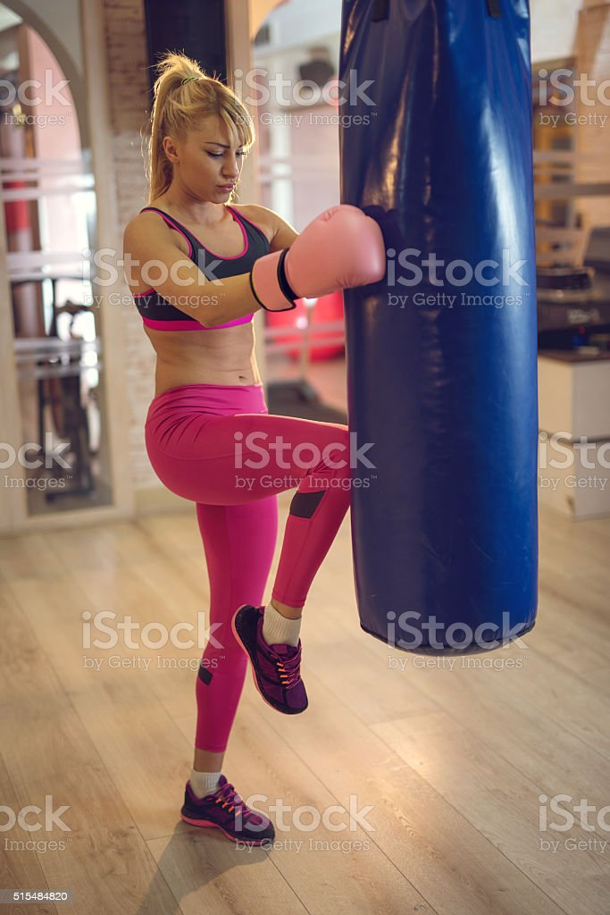 Female boxer exercising kick-boxing in a health club. stock photo