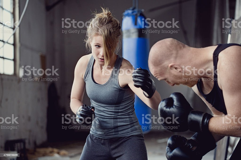 Female boxer sparring with her trainer stock photo