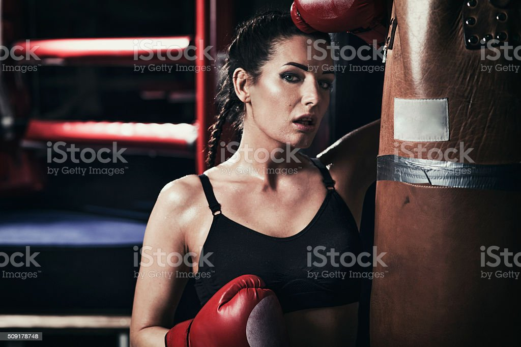 Female boxer standing by a punching bag stock photo
