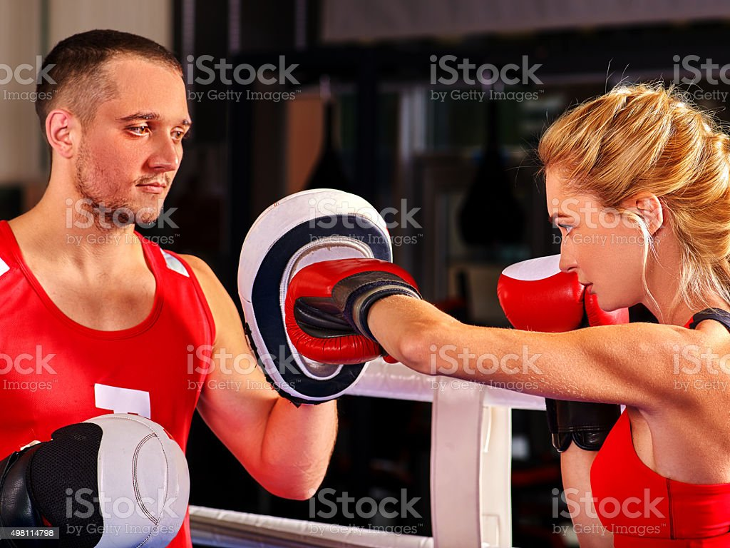 Female boxer  throwing  right cross at mitts stock photo