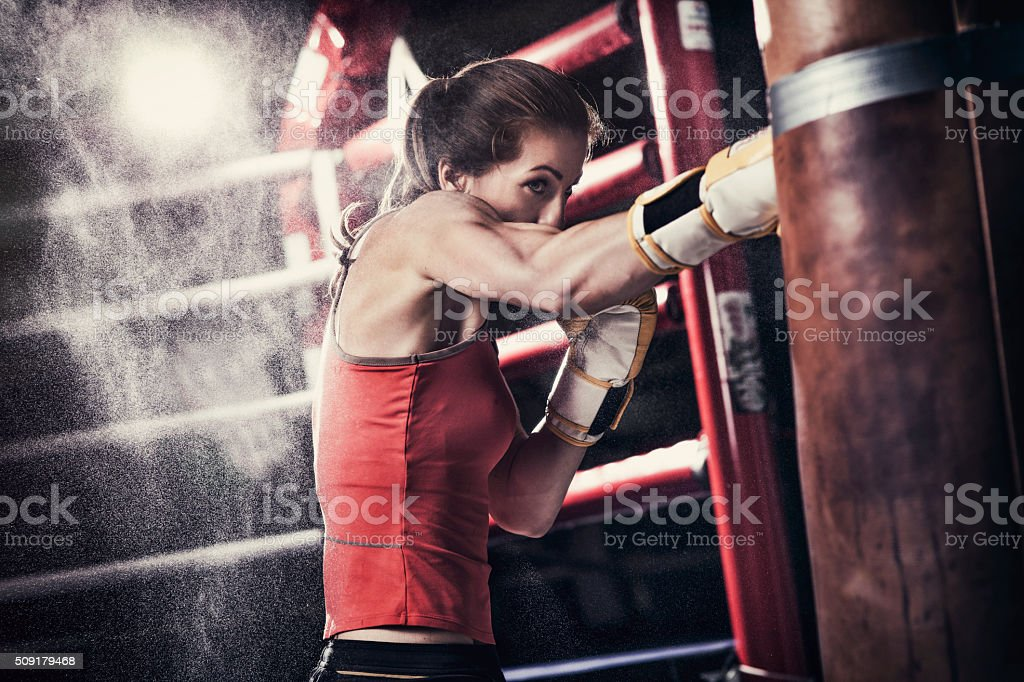 Female boxer training with a punching bag stock photo
