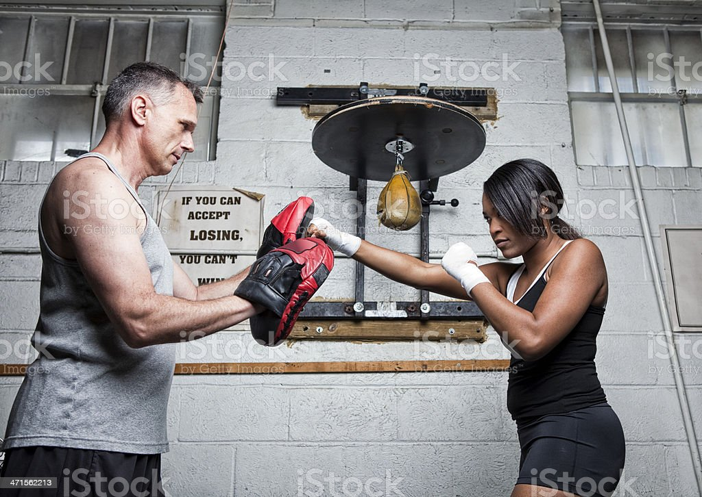 Female Boxer Training with Coach in the Gym royalty-free stock photo