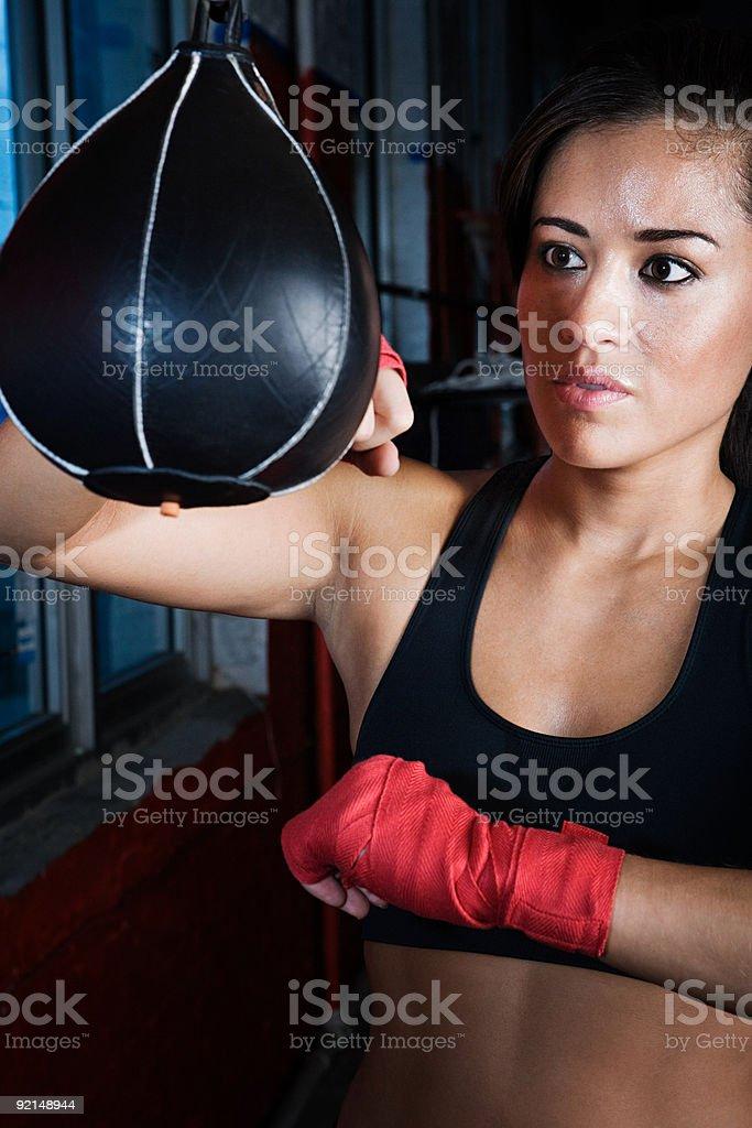 Female boxer using punch bag stock photo