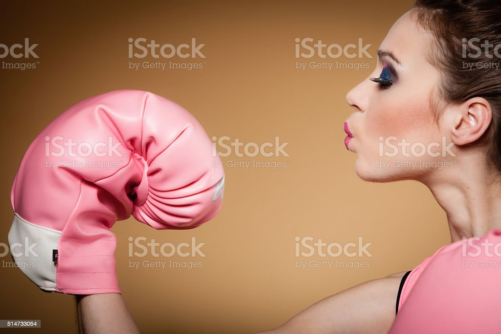 Female boxer wearing big fun pink gloves playing sports stock photo