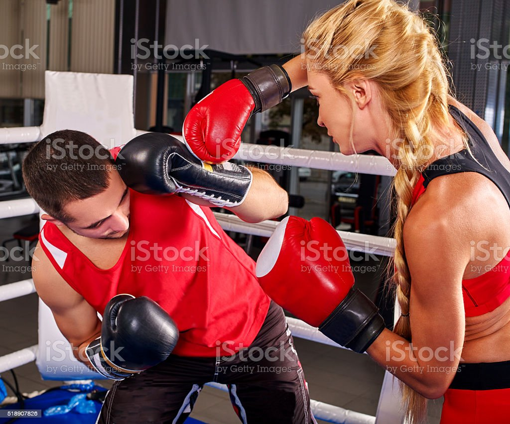 Female boxer with male coach on workout. Girl shoots  man stock photo
